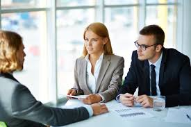 your career smart ways to make the best first impression in two serious business partners listening attentively to young man at meeting in office