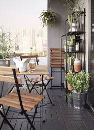 a small balcony furnished with a foldable table and three foldable chairs all in solid balcony furnished small foldable