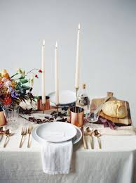 home decor edit moody table setting with tall candlesticks and linen tablecloth on tho