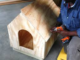 How to Build a Simple A Frame Doghouse   how tos   DIYalign roof panel  Man constructs a doghouse
