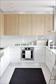 small u shaped kitchen design: neutral u shaped kitchen in white color and wood cabinets also dark rugs