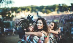 Three young <b>women</b> at a <b>summer</b> music <b>festival</b> feather headdress ...