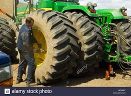 a tire technician works to change a tractor tire in the field a tire technician works to change a tractor tire in the field during planting season