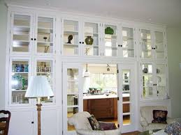 white kitchen windowed partition wall: display wall of see through glass cabinets between kitchen and grand dining room we will