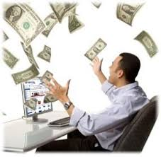 Man at a computer throwing money in the air