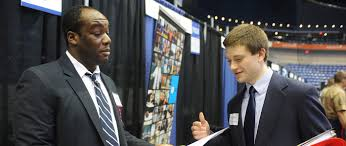 for employers umass lowell david chieh iii verizon corporate recruiter looks over jonathan campelli s resume at the career fair