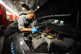 eve kobayashi 19 tests the battery of a car she is working on at porter dealership