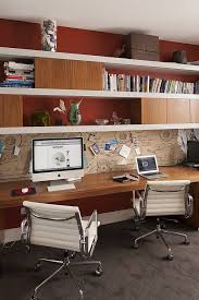 office workspace shared workspace warm tones rust colored walls warm woods white leather office chairs old world map like wall paper basement office setup 3 primary