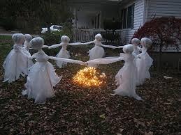 ideas outdoor halloween pinterest decorations: spooky halloween ghosts surrounding fire on frontyard at night