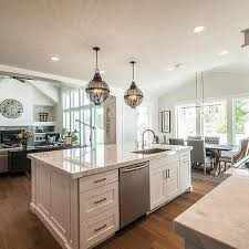build kitchen island sink: beautiful kitchen features a pair of black cage lanterns placed above a white center island topped with white quartzite countertops fitted with an off set