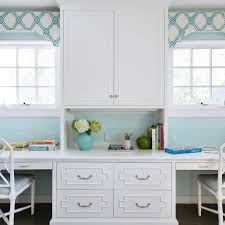 white and turquoise blue home office features white cabinets accented with bamboo overlay trim flanked by built in desk paired with white bamboo chairs with blue white home office