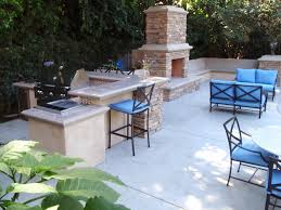 patio outdoor stone kitchen bar: outdoor kitchen area with stone fireplace blue outdoor seating with table bar area with grill concrete floor and tree wall for privacy