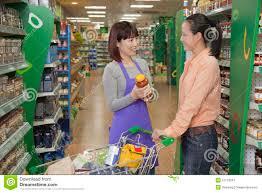 s clerk assisting women holding jar in the supermarket s clerk assisting women holding jar in the supermarket beijing