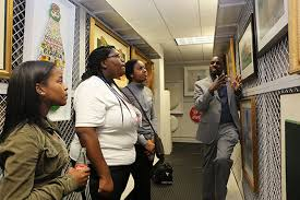 career exploration at coca cola a photo essay   cehd jamal booker explains framed coca cola artwork to early college students