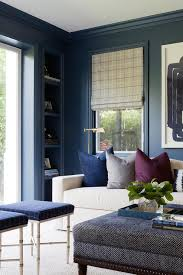 navy blue molding line navy blue home office walls framing a built in navy blue recessed shelf positioned adjacent to a window dressed in a gray check roman blue office walls