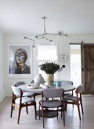 chair dining tables room contemporary: modern dining room with round dining table gray upholstered dining chairs and a modern globe