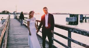 <b>bride and</b> groom standing on <b>wooden</b> dock near body of water photo ...