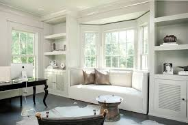 chic office features a bay window filled with a curved built in window seat adorned with metallic pillows flanked by floor to ceiling built in shelves chic home office features