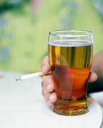 hand holding a cigarette and a beer