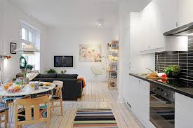 bright lighting inside small apartment design with white kitchen counter and round dining table set small apartment design ideas maximizing comfort in