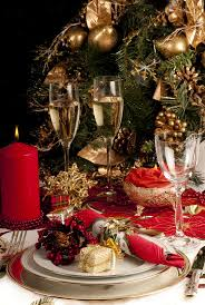 household dining table set christmas snowman knife: christmas dinner place setting with christmas table cloth plates knife and fork small presents candles christmas decorations champagne and wine glass