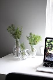 christmas tree branches in mini vases on desk in home office christmas tree office desk