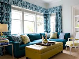 storage solutions living room: transitional living room using yellow tufted ottoman as coffee table and storage with blue patterned curtains and sectional sofa