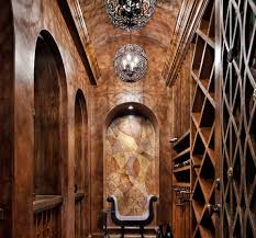 an elegant wine cellar with an inset on the back wall with a small settee barrel wine cellar designs