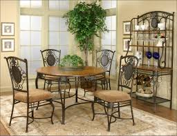 mid century design of round brown finish wood tops kitchen table with black wrought iron frames and 4 pieces mocha upholstery slip cushion seat dining black wrought iron furniture