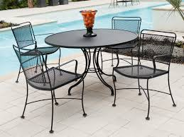 round black iron table with four curving legs combined with black chairs with nets and thin black iron outdoor furniture