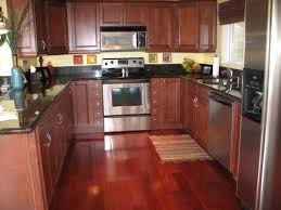 shaped kitchen island black granite countertop redborwn cabinetry with u shaped kitchen layouts also wooden laminatin