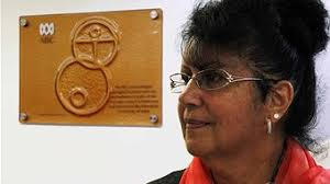 Artist Judith-Rose Thomas and the plaque that she designed for the ABC studios in Launceston (Tim Walker - ABC Local) - r1122517_13756383