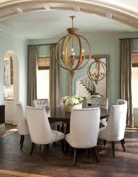 chair dining tables room contemporary: plush dining chairs contrast with dark wood circular dining table a large gilded mirror