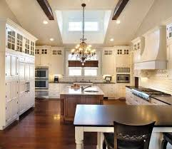 countertops dark wood kitchen islands table: vaulted ceiling with exposed dark wood beams in this white kitchen over natural wood flooring