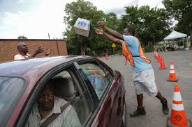 flint water crisis a visual essay water water everywhere ivante johnson right of flint tosses a case of water to michael osborn to load into a vehicle while working at a community pod water distribution site at