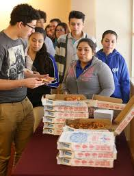 mentoring program helps teens financial goals after high big brothers big sisters participants line up for pizza during a christmas holiday lunch dec