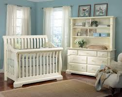 lush white wood construction crib and matching dresser stand over dark hardwood flooring in this nursery boy nursery furniture