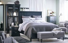 a large bedroom with a big black bed standing in the middle of the room bedroom furniture at ikea