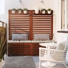 a balcony with brown wooden storage benches with seat cushions wall panels and shelves filled balcony furnished small foldable