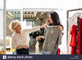 s assistant in clothes shop helping customer choose top s assistant in clothes shop helping customer choose top garment