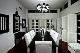 black and white dining table set: monochromatic dining room black dining table white dining chairs black crystal chandelier and black mirror