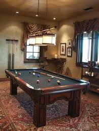 a lotus pattern oriental carpet and antique pool table imbue this playroom with the elegance billiard room lighting