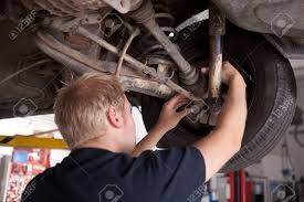 a male mechanic inspecting a cv joint on a car in an auto repair a male mechanic inspecting a cv joint on a car in an auto repair shop stock