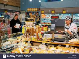 riga interior of rimi hypermarket n store assistant interior of rimi hypermarket n store assistant and customer at cheese dairy