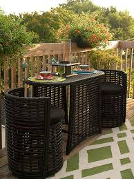 the round chairs tuck beneath the table disappearing into the oval shape of the synthetic wicker dining set patio furniture for small patios