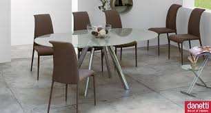 round glass extendable dining table: oval clean extendable glass dining table with round chrome legs and dark brown suede dining chairs