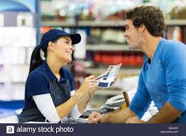 female paint store worker talking to customer over the counter stock photo female paint store worker talking to customer over the counter