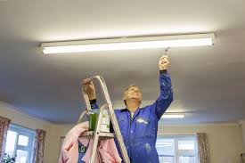 essential skills for work in the hospitality industry maintenance man fixing overhead light in office