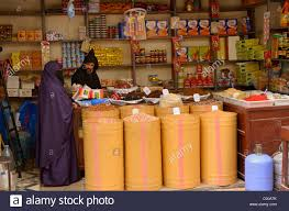 grocery store worker in djellaba female customer in purple grocery store worker in djellaba female customer in purple hijab in fes el bali medina fez north africa