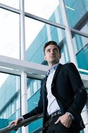 young elegant man after graduating ready to start new adult life stock photo young elegant man after graduating ready to start new adult life view from the bottom of student in suit on college